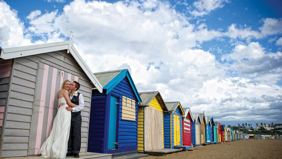 Married couple kissing in front of multi-coloured beach bathing boxes.