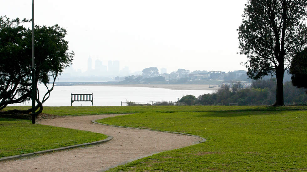 Pathway leading through grass and to a foreshore bench overlooking Port Phillip Bay and Melbourne CBD skyline.