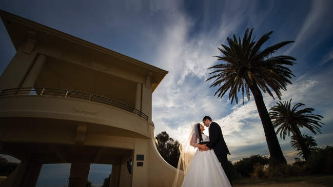 Recently married couple embracing in front of rotunda and palm tree.