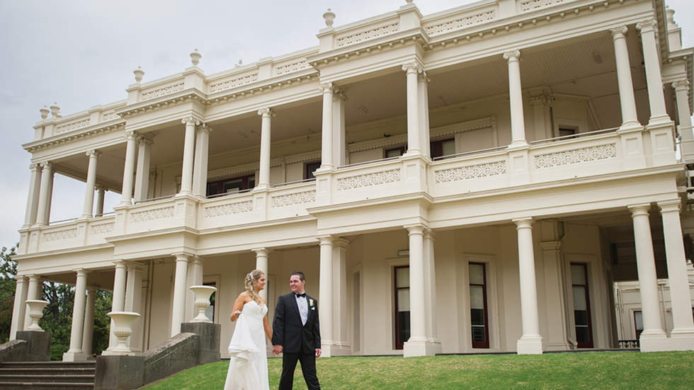 Recently married couple walking holding hands in front of grand mansion.
