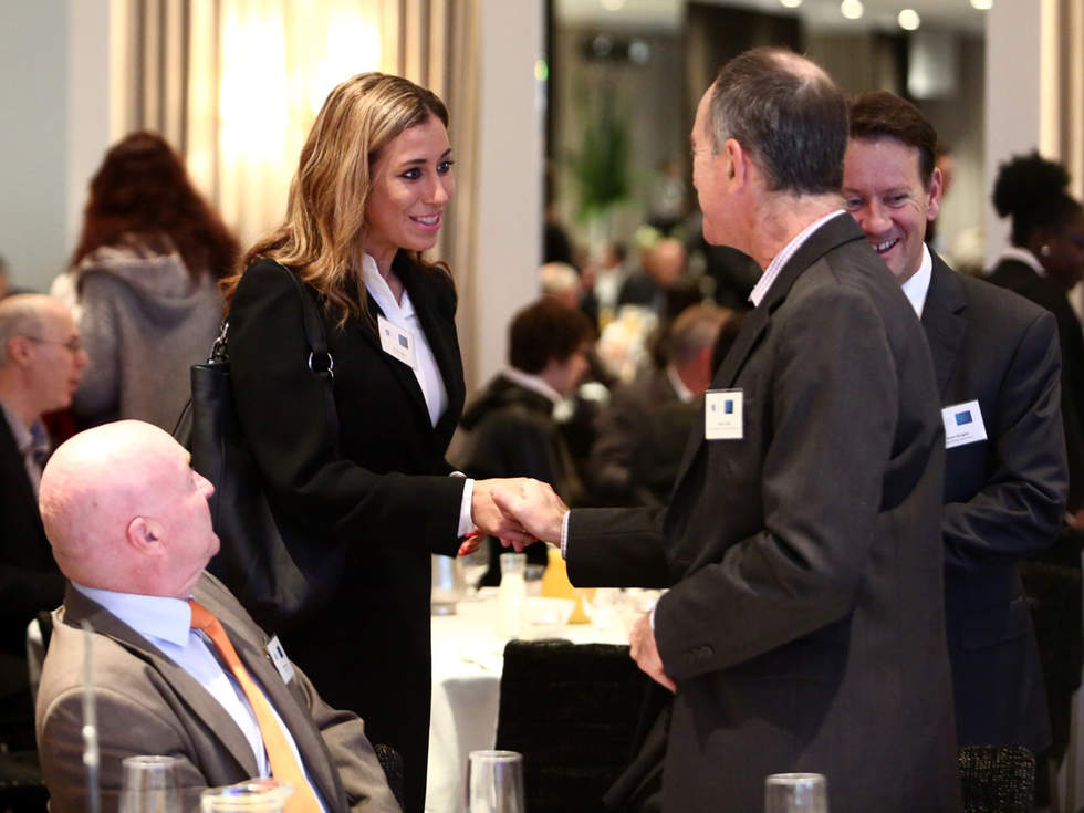 Businessman greeting businesswoman at Bayside Business Network 2016 breakfast