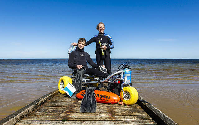 Disabled diver sitting on equipment and person standing at edge of water at beach