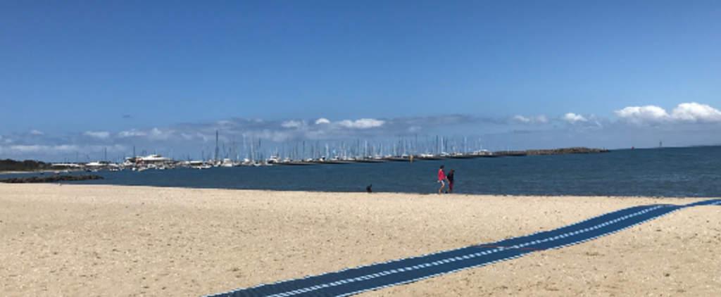 Two people walking along Hampton beach with Hampton Sailing club in background