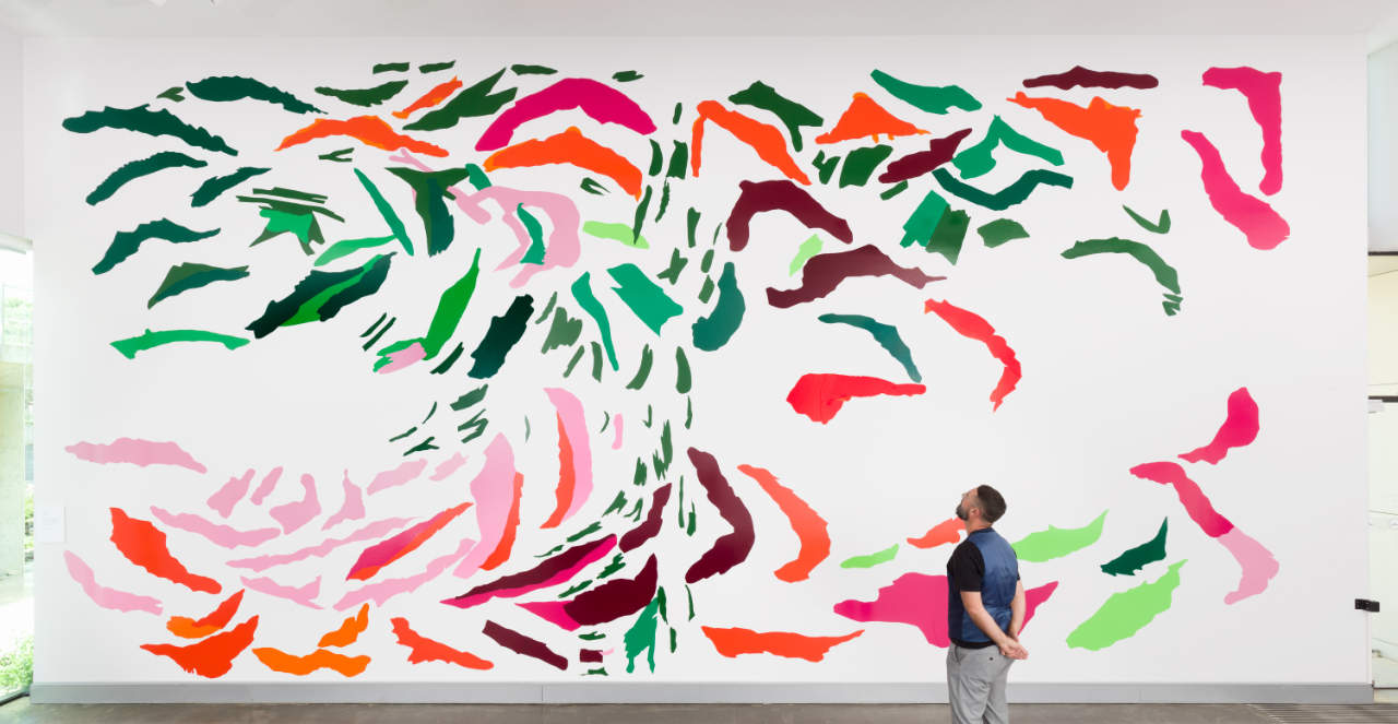 A man looks up towards a colourful artwork of elongated shapes adhered to a large white wall.