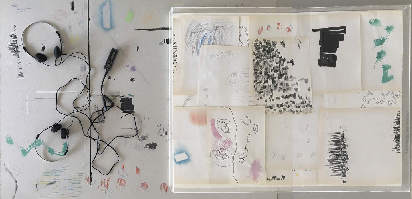 An overhead view of two sets of headphones and loose drawings depicting lines and marks.