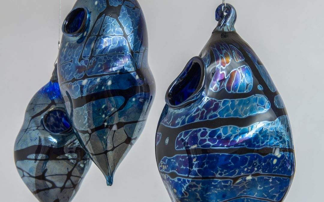 Three retort shaped, suspended nests made from glass. Each nest has a hole, there is a blue and black pattern on the surface.