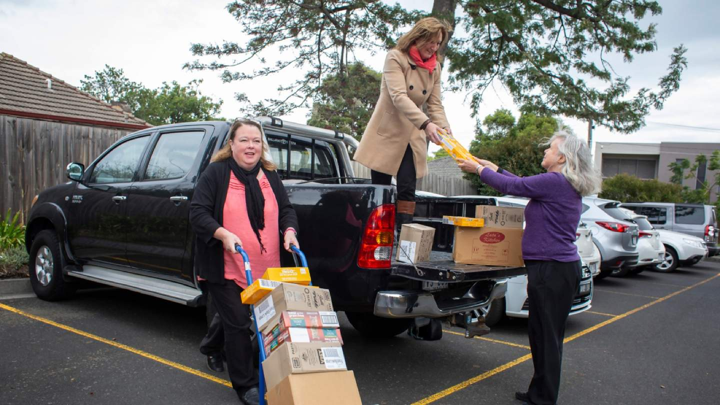 Women pushing parcel trolley and women in back of ute handing parcels to another women