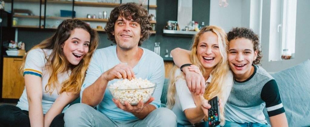 Family eating popcorn watching movie.