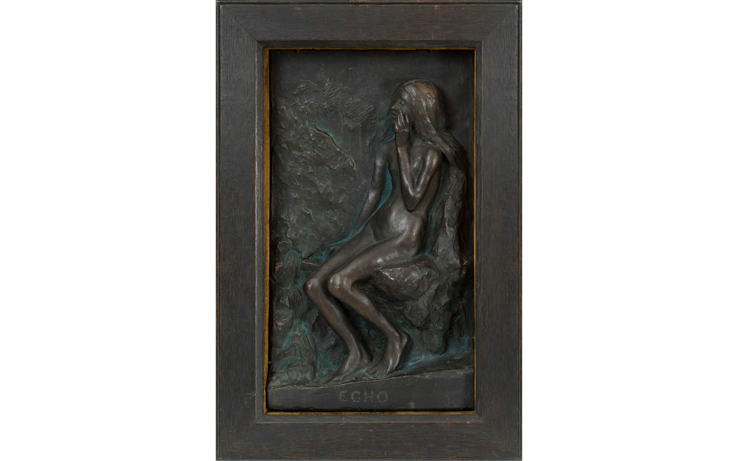 A relief sculpture in dark bronze of a nude female figure is seated in a rock formation, under which the word ECHO is spelt.