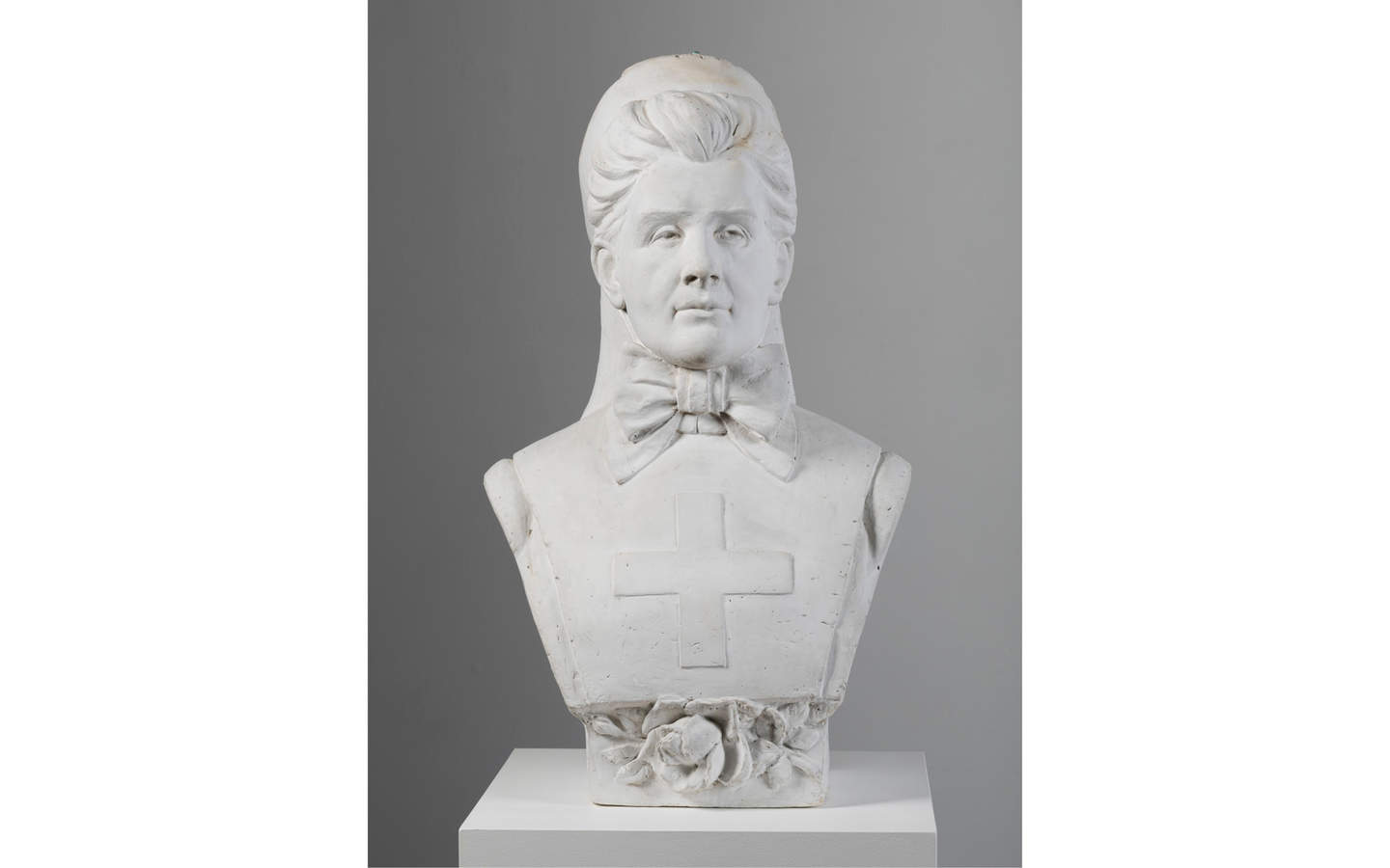 White plaster bust of a woman on a white pedestal. The woman is wearing a stiff, flat garment with medical cross on the chest and a large bow at the neck.