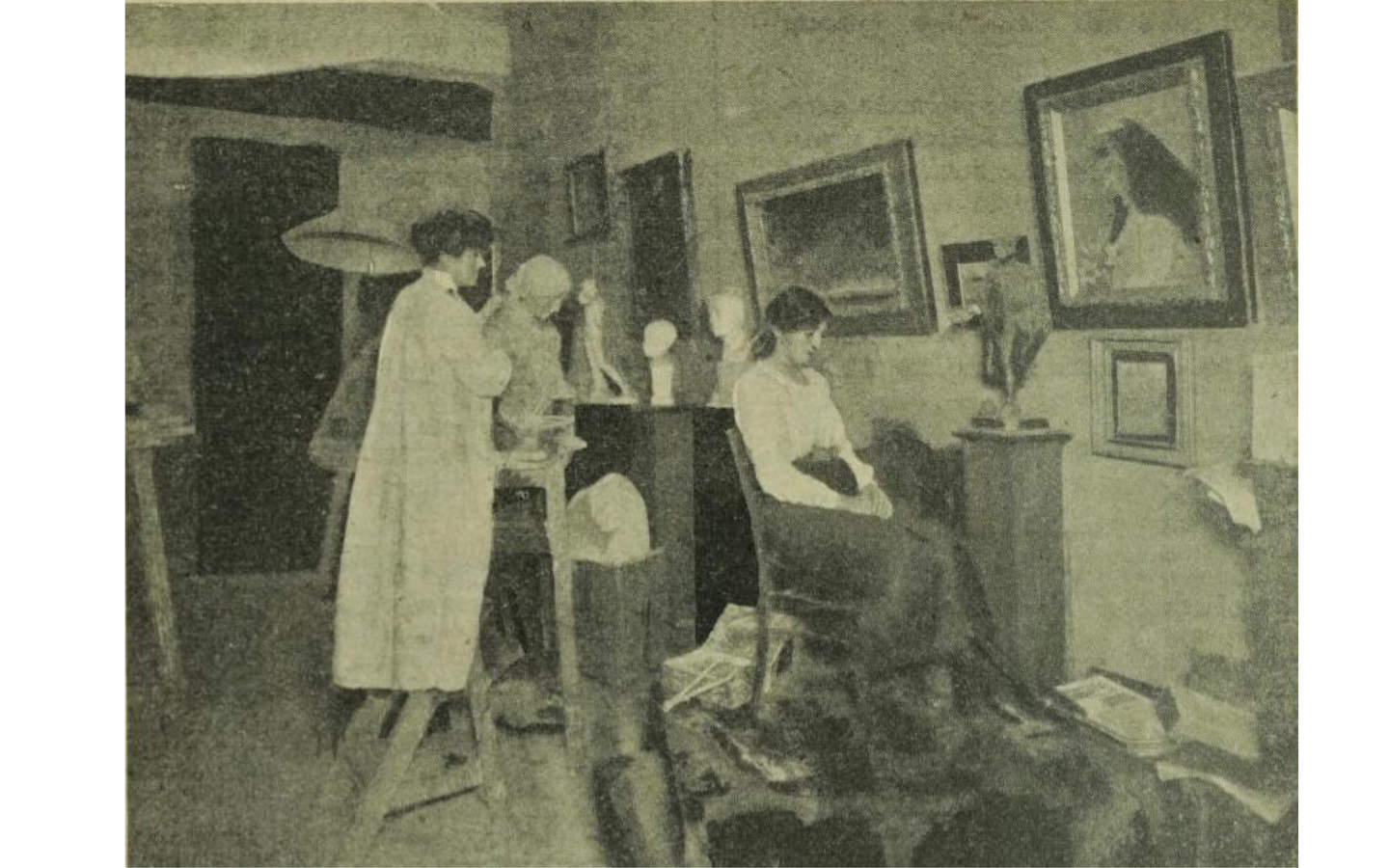 Black and white photograph of an artist in her studio surrounded by paintings and sculptures. The artist wears a white smock and stands on a ladder next to a sculpture while her model is seated in front of her.
