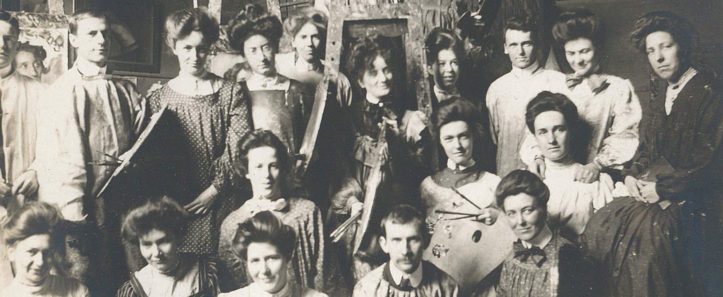 Black and white photograph of women and men student artists seated and standing, wearing art smocks, some holding painting palettes, with easels in the background