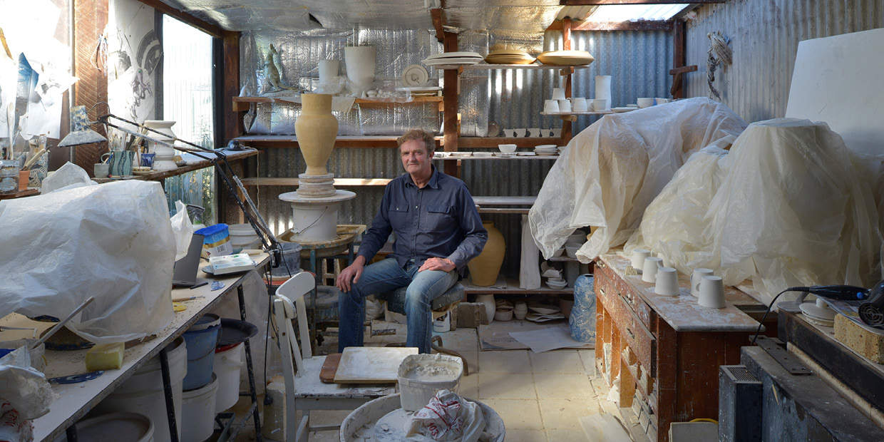 Artist Gerry Wedd in his studio, surrounded by various ceramics and pottery making tools